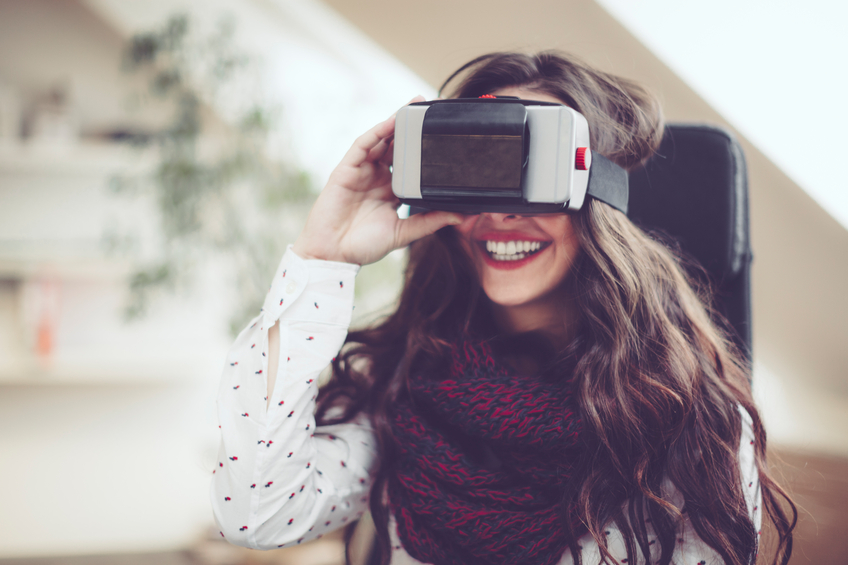 Young woman is using head-mounted virtual reality goggles